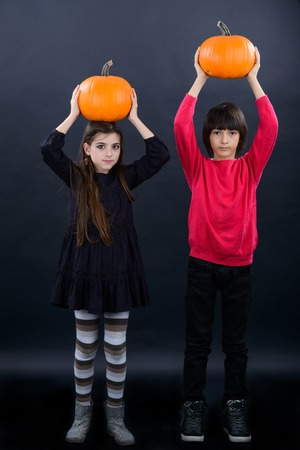 Boy and girl wearing halloween costume with pumpkin on black  background photo
