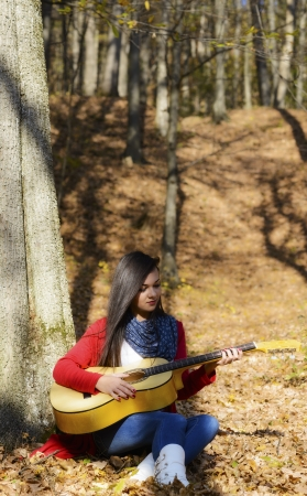 Beautiful brunette guitar player girl in the forest photo
