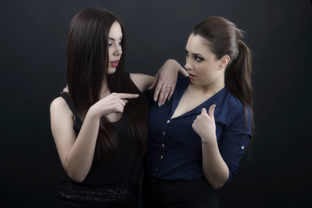 Two girls looking at each other isolated on black background photo