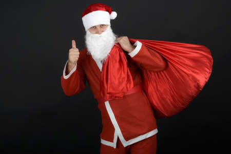Santa Claus with christmas sack  isolated on black background photo
