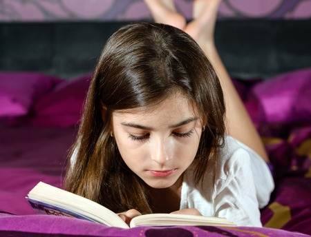 leisure reading girl is comfortable lying on her bed with a book Stock Photo