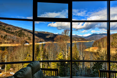 a picture window with a view of mountain lake