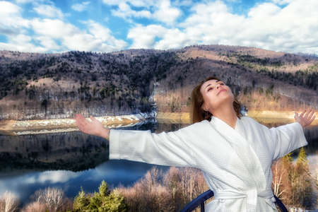 woman relaxes by looking at a mountain landscape