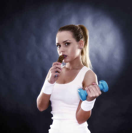 young healthy girl eating a cereal bar over a black background photo