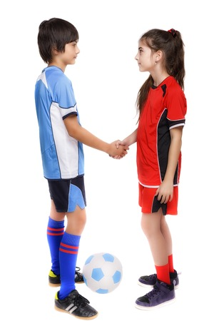 two children boy and girl shaking hands after football game Stock Photo