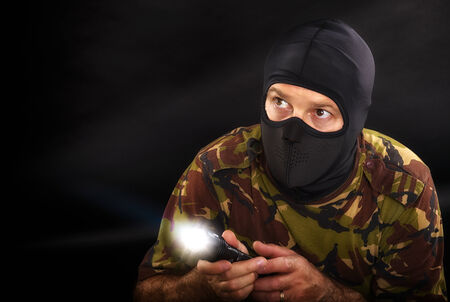 guerilla: soldier on a black background with a flashlight in camouflage military outfit