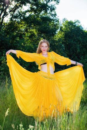 beautiful woman in yellow dress posing in nature photo