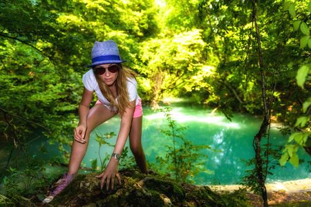 tourist woman walking through the woods along a river photo