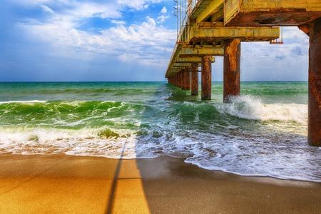 old bridge hit by waves at sea photo