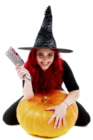 atrocity: witch with bloodstained hands with a hatchet in hand sits on a pumpkin Stock Photo