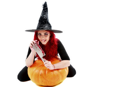 witch with bloodstained hands with a hatchet in hand sits on a pumpkin photo
