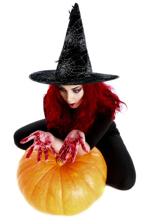 atrocity: witch with bloodstained hands  sits on a pumpkin Stock Photo