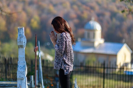 young woman prays in front of a cross in the cemeter photo