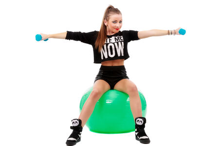 young sporty woman sitting on fitball with dumbbells on white background photo