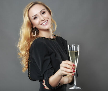 beautiful elegant woman with a glass of champagne in hand isolated on gray Foto de archivo