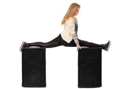 splits: female dancer doing the splits on two speakers Stock Photo