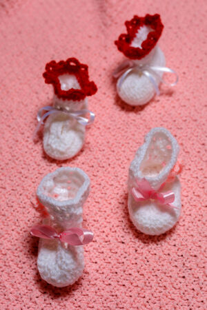 baby's bootee: baby little shoes on carpet pink Stock Photo