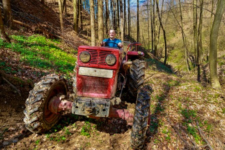 wheel tractor: farmer driving a old tractor in forest