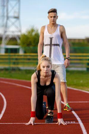 concurrencer: Jeune couple de sport en position de d�part pr�t � soutenir la concurrence et de fonctionner