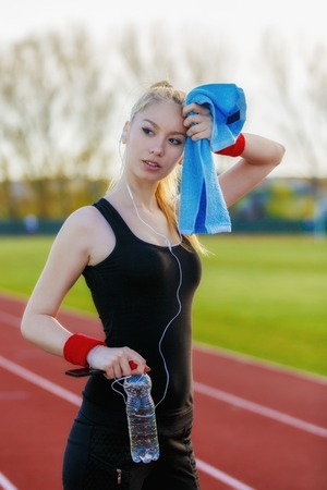 Young sporty woman holding water bottle and wiping sweat with a towel