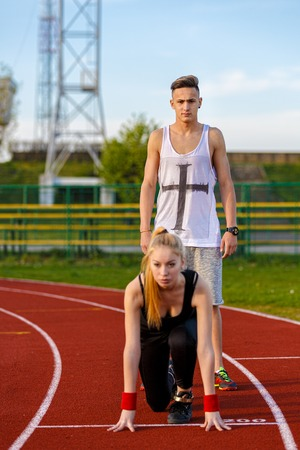 rival rivals rivalry season: Young sport couple in starting position prepared to compete and run
