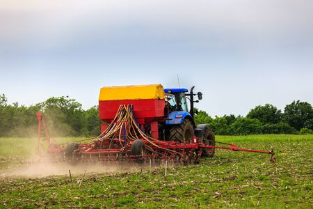 industrialized country: agricultural work plowing land on a powerful tractor Stock Photo