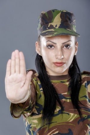 sufficient: Soldier woman showing palm stop sign on gray background Stock Photo