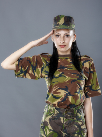 saluting: Woman army soldier saluting isolated on gray background