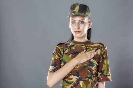 swear: Army soldier swear solemnly with hand on heart to defend country