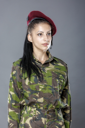 camoflauge: portrait of a woman soldier isolated on gray background
