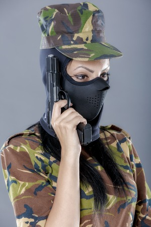 female assassin: Female soldier in camouflage uniform with weapon isolated on gray background