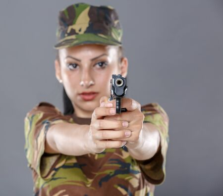 special agent: Female soldier in camouflage uniform with weapon isolated on gray background