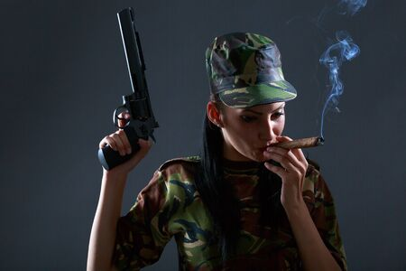 cigar smoke: Female soldier in camouflage uniform with gun and cigar smoke Stock Photo