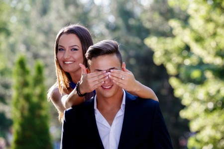expressing: Photo of a woman covering the eyes of a man