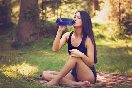 plant nature: Beautiful woman relaxing and drinking water, sitting in  garden, on blanket