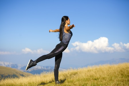 Exercising fitness woman doing exercises in nature. Girl doing mountain climbers exercise training outside in amazing landscape on Iceland. Fit female Asian Caucasian athlete sport model