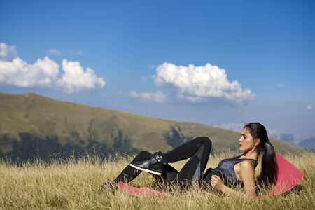 asian abs: Exercising fitness woman doing exercises in nature. Girl doing mountain climbers exercise training outside in amazing landscape on Iceland. Fit female Asian Caucasian athlete sport model