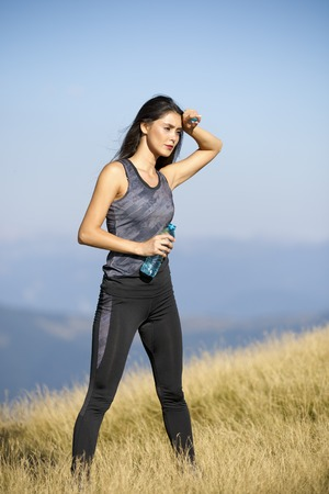 hot day: A beautiful sporty caucasian girl drinking water after exercise