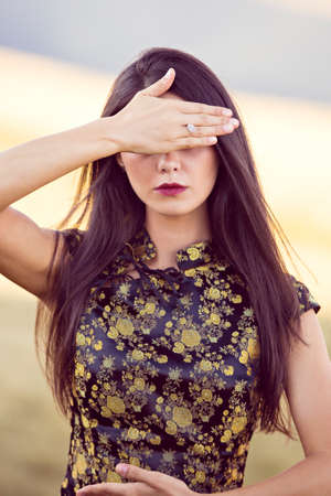 covering eyes: beautiful woman covering eyes with hands Stock Photo