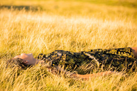 lies down: woman lies down in the grass yellow Stock Photo
