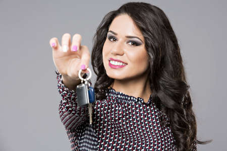 handing over: Young saleswoman handing over car keys, isolated on gray background