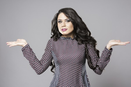 i dont know: business woman shrugging with I dont know gesture, isolated on gray background Stock Photo