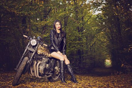 Biker girl in a leather jacket on a motorcycle posing in nature