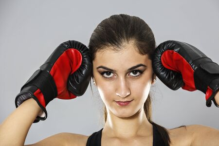 woman with boxing gloves: sport young woman boxing gloves, face of fitness girl studio shot over gray background
