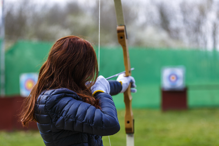 bowman: woman archer shooting with his bow at an outdoor archery range