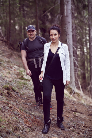 forested: A woman and a man are trekking in the forested mountain Stock Photo
