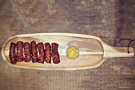 barbequing: Traditional food Meat Balls mici on a rustic wooden table with mustard