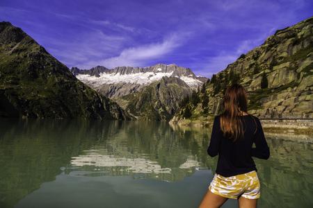 Women admire a beautiful mountain landscape with lake