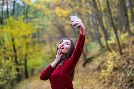 Young caucasian brunette woman with headphones outdoors on autumn day