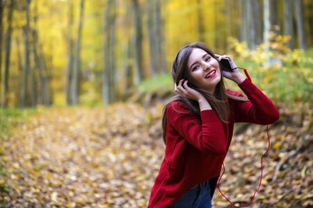 autumn young: Young caucasian brunette woman with headphones outdoors on autumn day